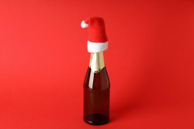 赤い背景にサンタの帽子とシャンパンボトル。