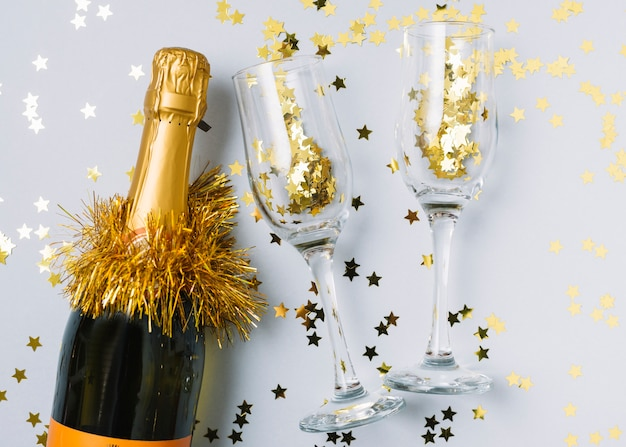 Champagne bottle with small spangles in glasses