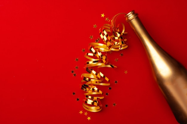 Champagne bottle with sparkling confetti on red background flat lay top view