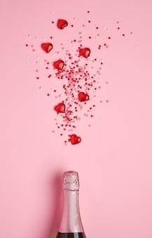 ピンクの背景の上に赤いハート型の紙吹雪と装飾的なハートのスプラッシュとシャンパンボトル。バレンタインデーのコンセプト。上面図、コピースペース。