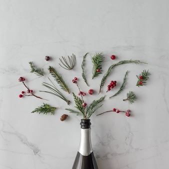대리석 벽에 겨울 단풍과 샴페인 병입니다. 평평하다. 파티 개념.