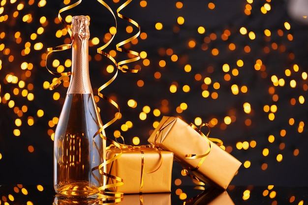 Champagne bottle and wrapped gift on blurred background of christmas lights front view