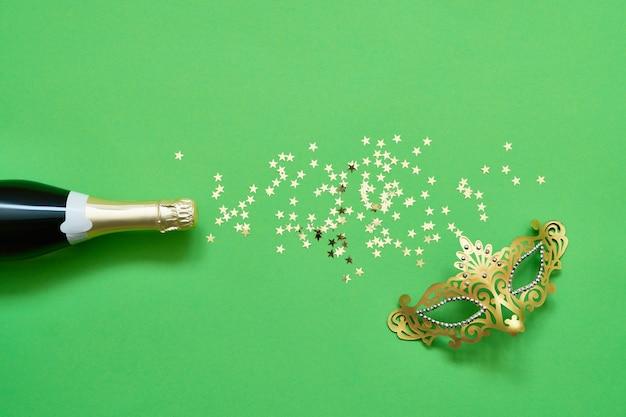 Бутылки шампанского, золотая карнавальная маска и звезды конфетти на зеленом. рождество