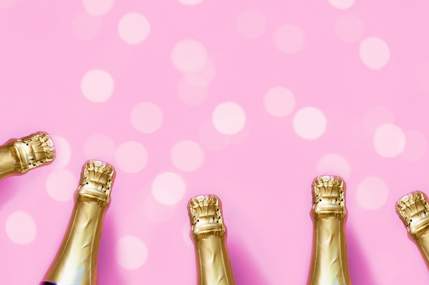 Champagne bottles on a pastel pink background with bokeh lights