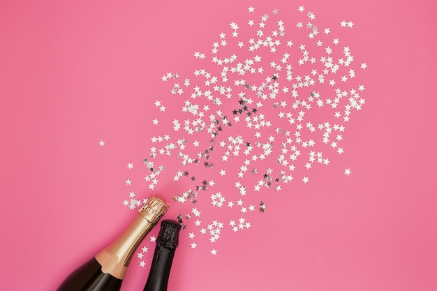 Champagne bottles with confetti on pink background.