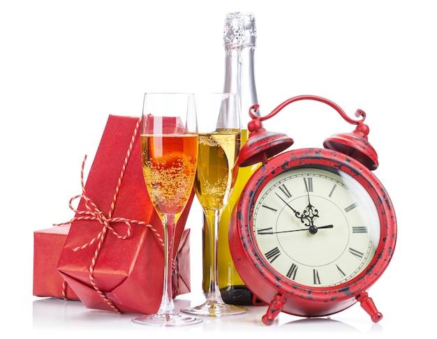 シャンパン、クリスマスプレゼント、目覚まし時計。白い背景で隔離