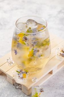 明るい灰色の背景に氷と花とシャンパンカクテル