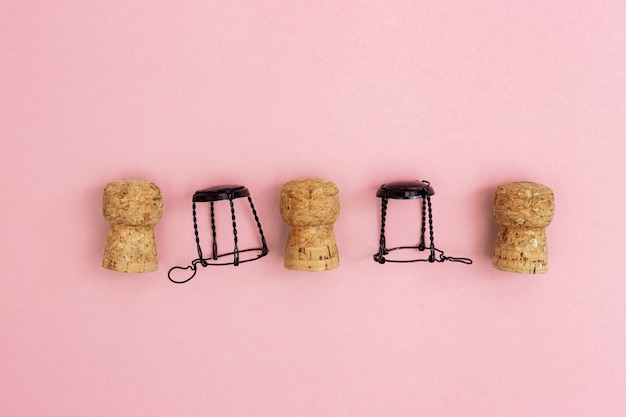 Champagne corks and muselets on pink paper background with copy space. close up used wooden stoppers. concept for party or holiday.