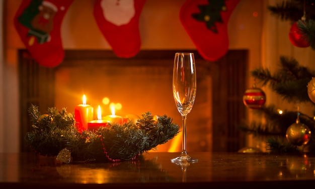 Champagne flute on christmas dinner table in front of burning fireplace
