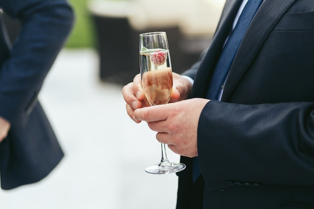 Champagne flute held by a man in black jacket