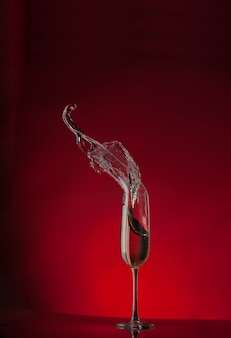 Champagne flute splash isolated on red