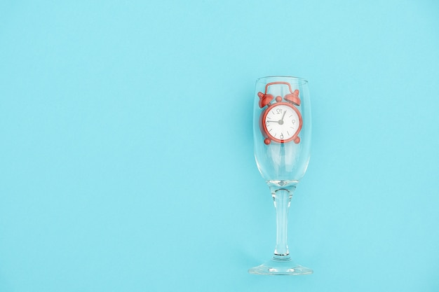 Champagne flute with red alarm clock inside on blue background