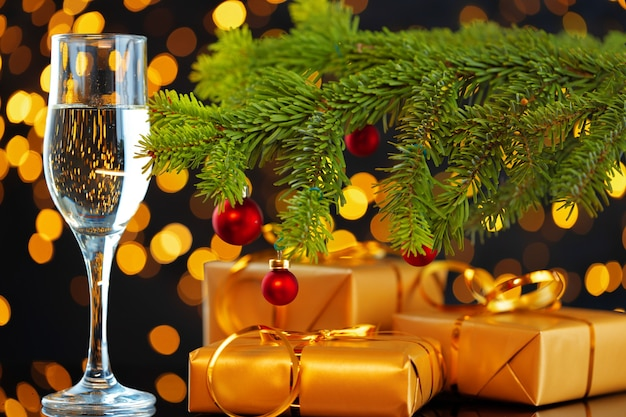 Champagne glass on blurred garland lights background close up
