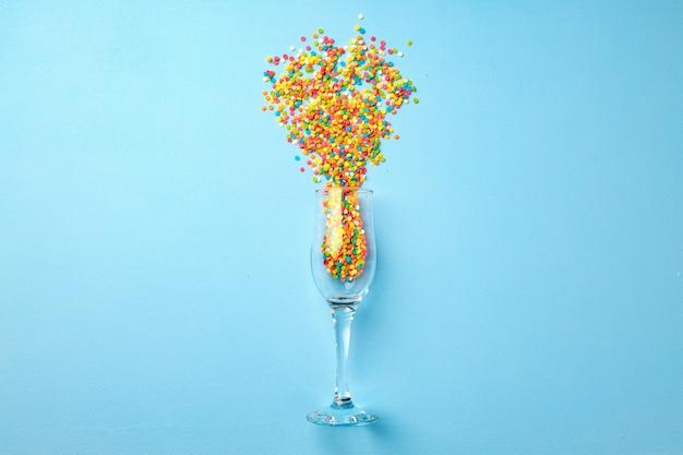 Бокал шампанского с конфетти, плоский вид сверху, новогодний фон