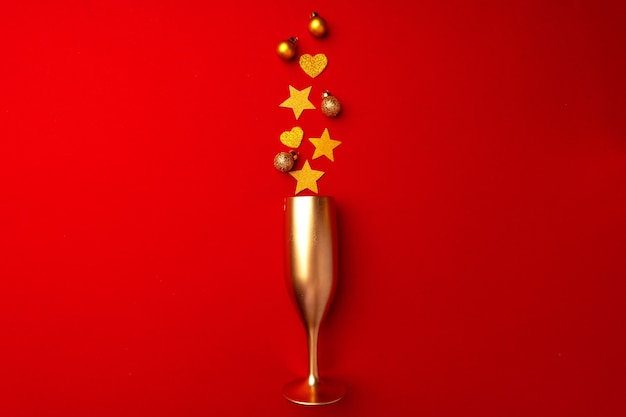 Champagne glass with glitter confetti on red background flat lay top view