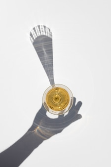 Champagne glass with long hard shadow of hand