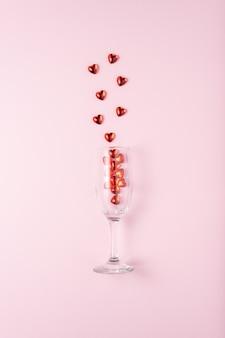 Бокал шампанского с сердечками красного стекла над розовой поверхностью.