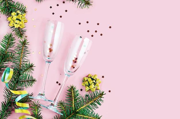 ピンクのフラットレイに輝きと紙吹雪のシャンパングラス