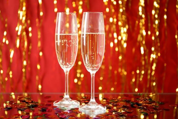 Бокалы для шампанского против цветового пространства с золотыми лентами, место для текста