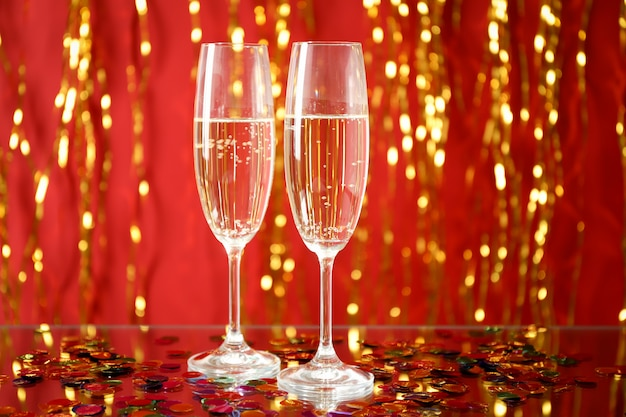 Champagne glasses against color space with golden ribbons, space for text