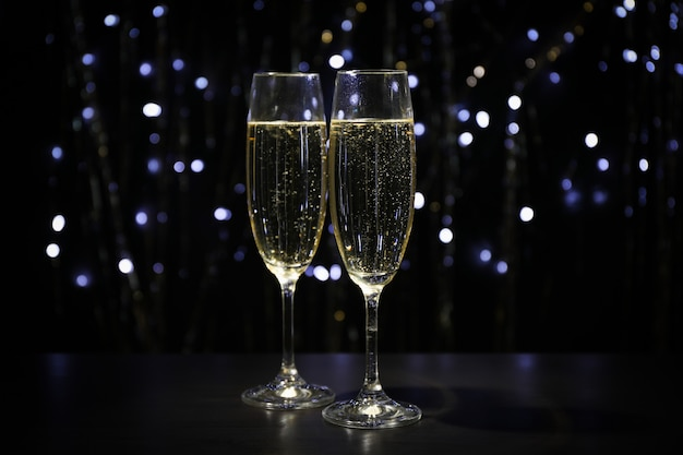 Champagne glasses against dark space with blurred lights, copy space