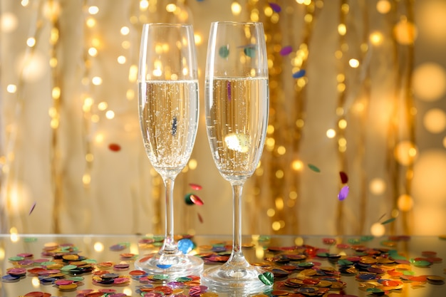 Champagne glasses against space with golden ribbons, space for text
