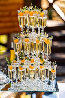 Champagne in the glasses against the wooden background. vertical stand of glasses. close up.