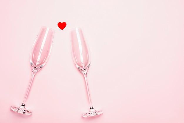 Бокалы для шампанского и красное сердце на розовом фоне.