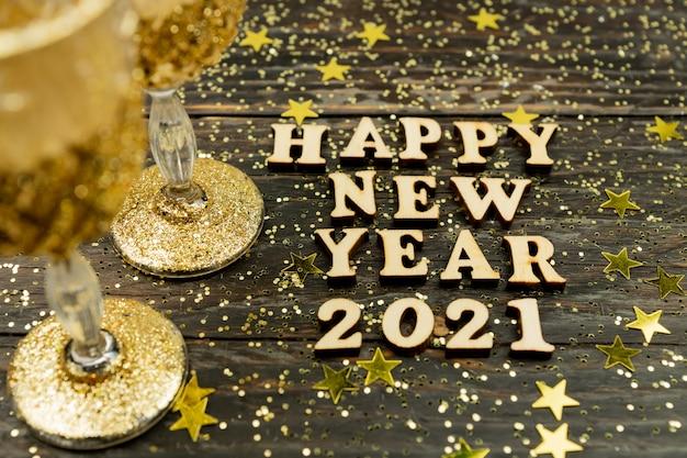 シャンパングラスとテキストの幸せな新年2021年木製