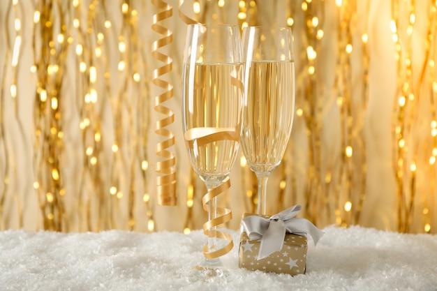 Бокалы для шампанского и подарок против пространства с золотыми лентами, место для текста
