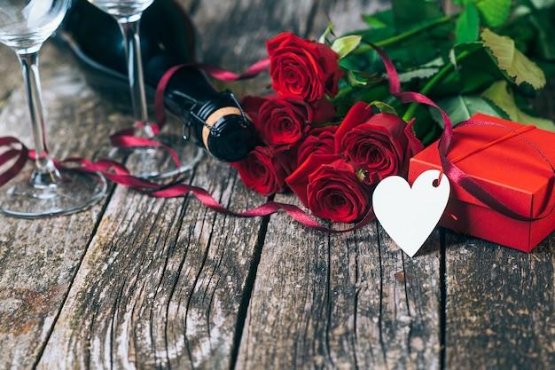 木の板のシャンパングラスとロマンチックなバラバレンタインデーカード