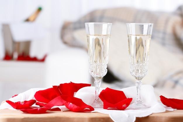 Бокалы для шампанского и лепестки роз для празднования дня святого валентина