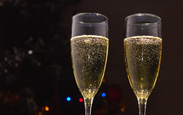 Champagne glasses on the background of a decorated christmas tree