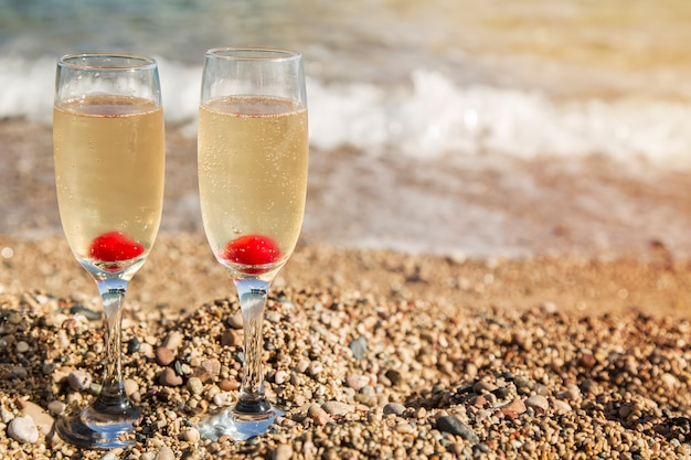 Champagne glasses on beach at sunset. two glasses of champagne on castle background.
