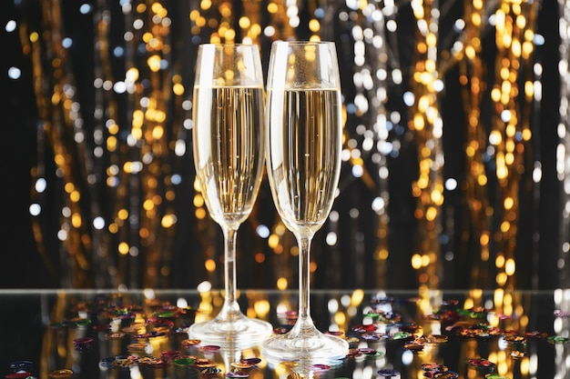 Champagne glasses on blurred space, space for text