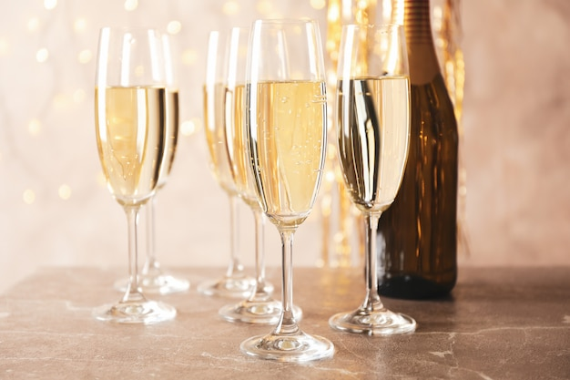 Champagne glasses and bottle against blurred lights space, close up