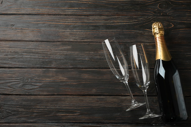 Champagne glasses and bottle on wooden space, space for text