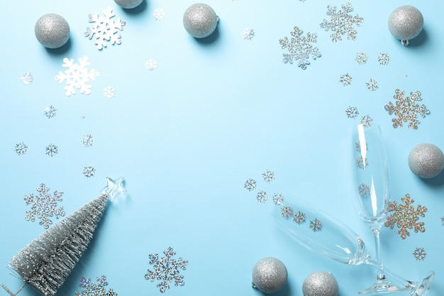 Champagne glasses and christmas baubles on blue, copy space