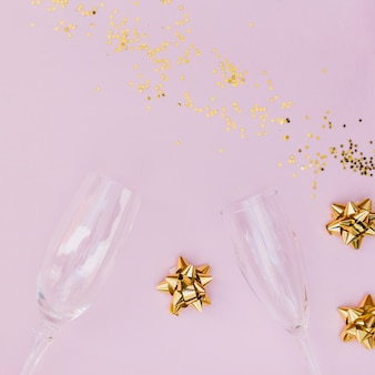 Champagne glasses; confetti and bow on pink backdrop