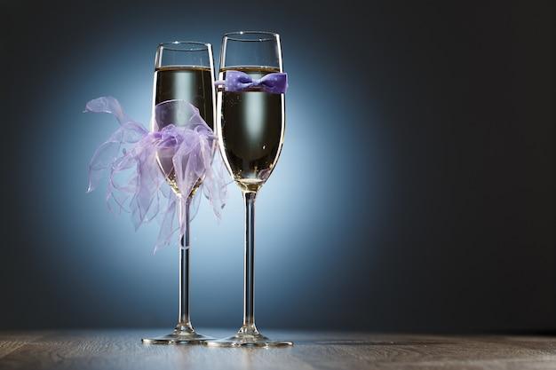 シャンパングラスは、新婚旅行者のために紫色の蝶ネクタイとベールを飾りました。明るいお祭りの青い背景の画像