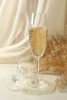 흰색 테이블에 샴페인 잔, 에폭시 수지 및 필드 꽃