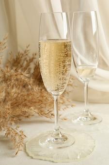 Бокалы для шампанского, эпоксидная смола и полевые цветы на белом столе