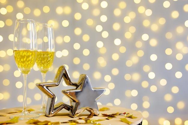 Champagne glasses over festive led lights background