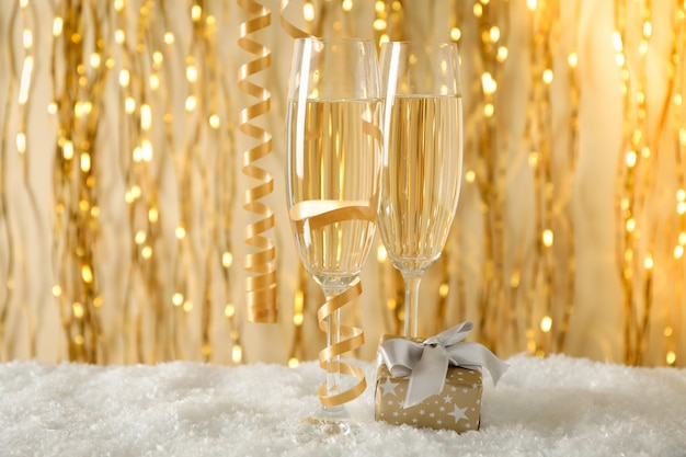 Champagne glasses and gift against space with golden ribbons, space for text