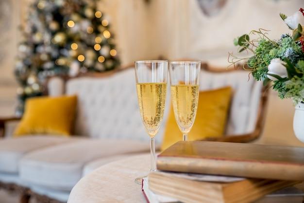 Champagne glasses over golden blinking christmas tree