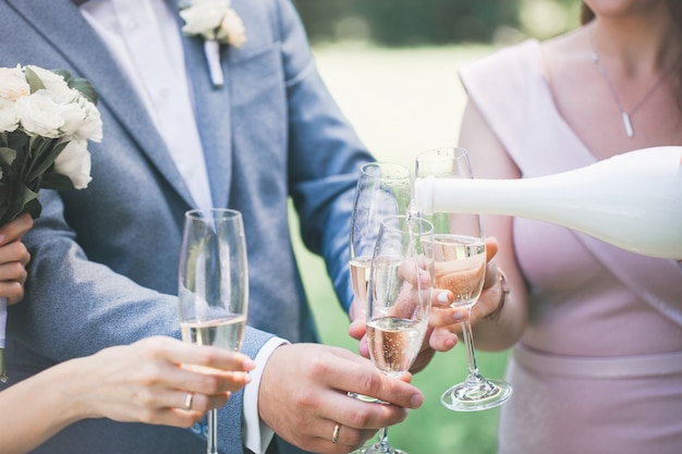Champagne in glasses in hands, close-up