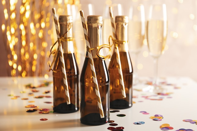 Champagne glasses and mini bottles on decorated space, space for text