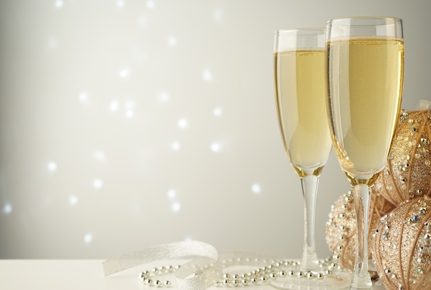Бокалы для шампанского рядом с елочными шарами и серебристо-белыми лентами