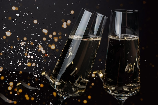 Бокалы для шампанского на темной стене со снегом и огнями. новый год, рождество