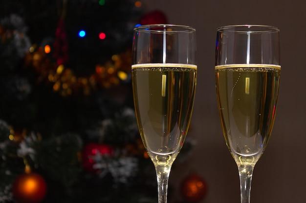 Бокалы для шампанского над украшенной елкой